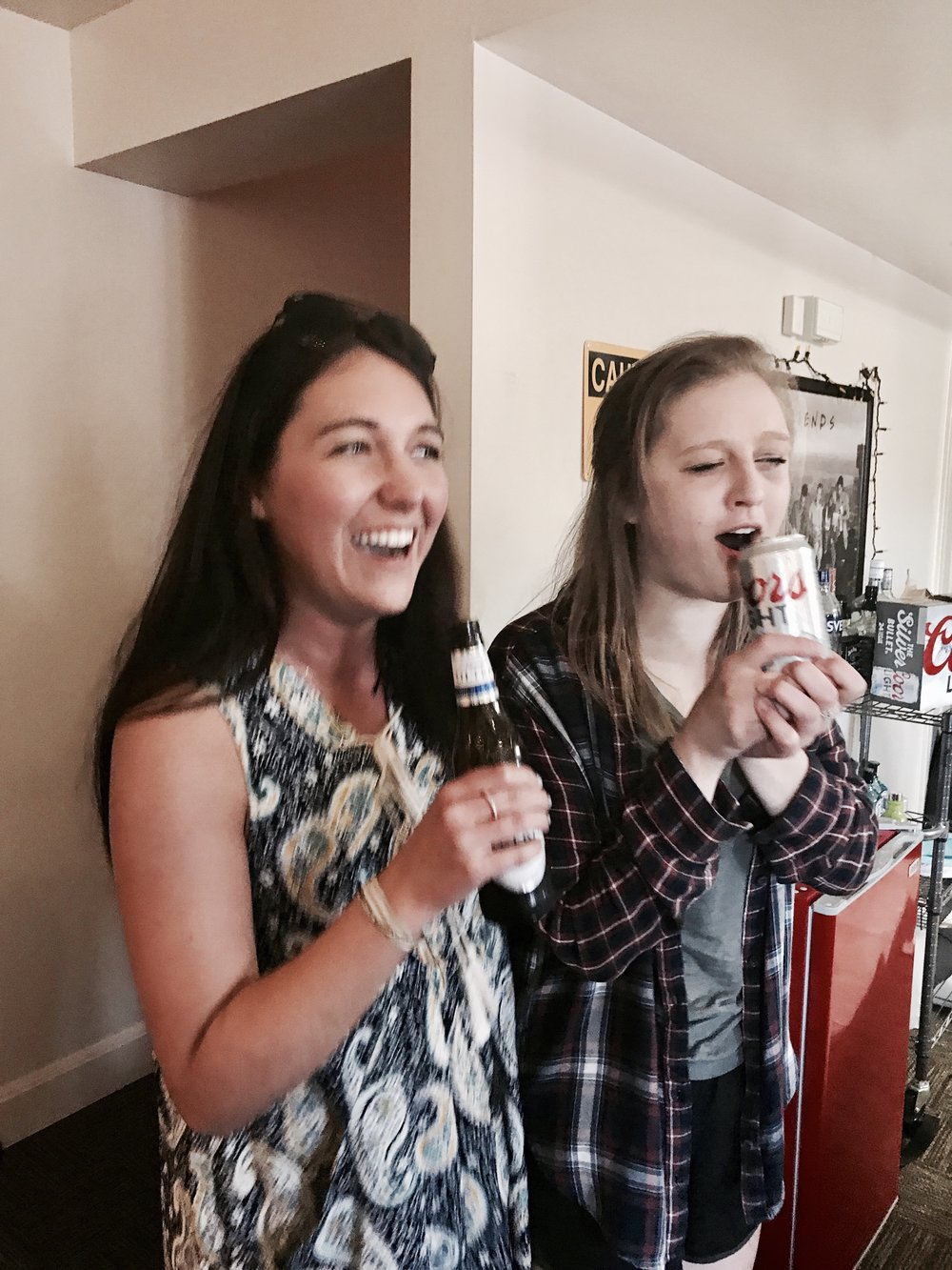 "Kaitlyn (left) and Julie (right) singing Billy Joel's ""Uptown Girl"" using beer bottles as ""microphones""."