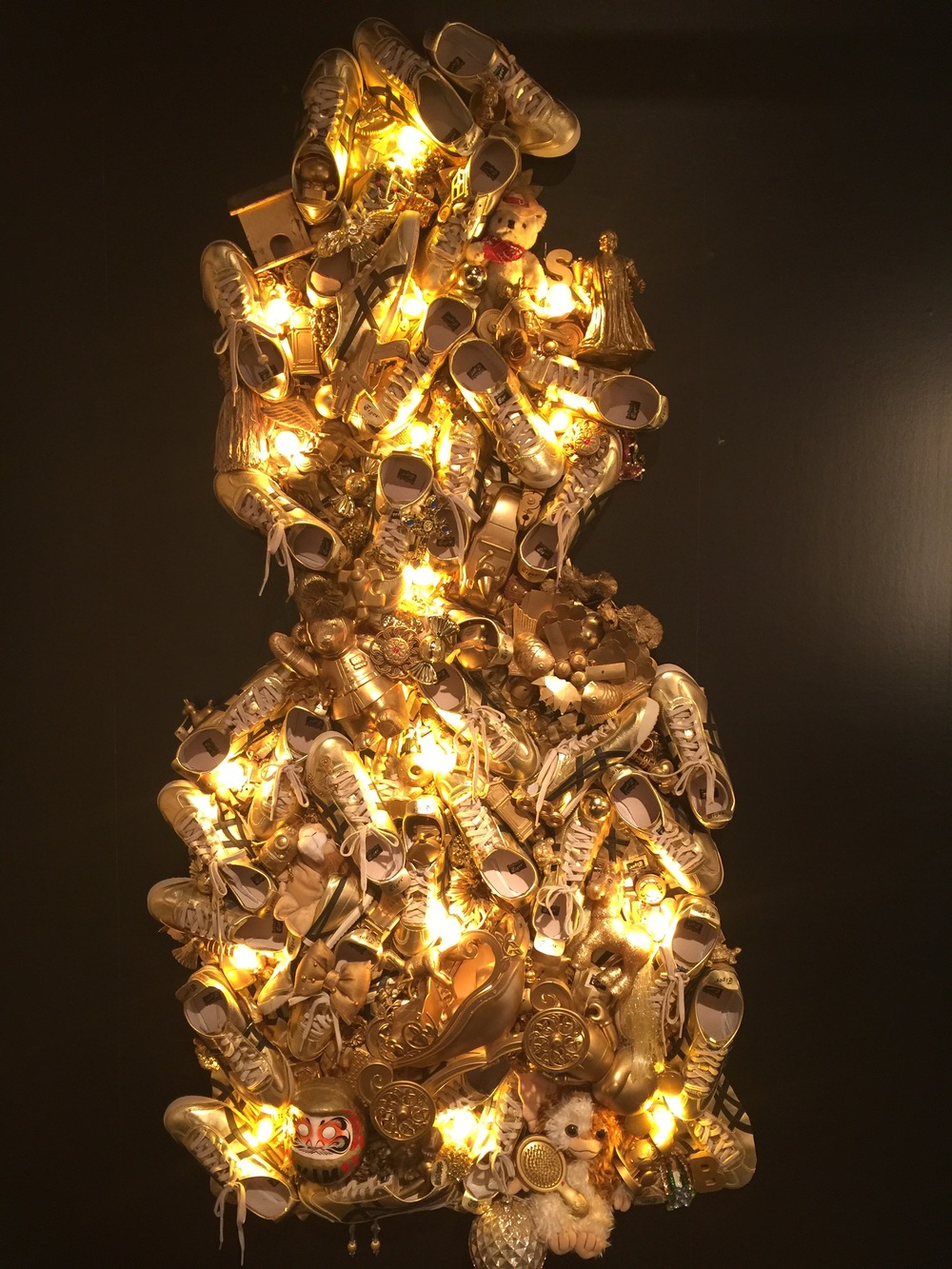 Gold light fixture of mostly shoes