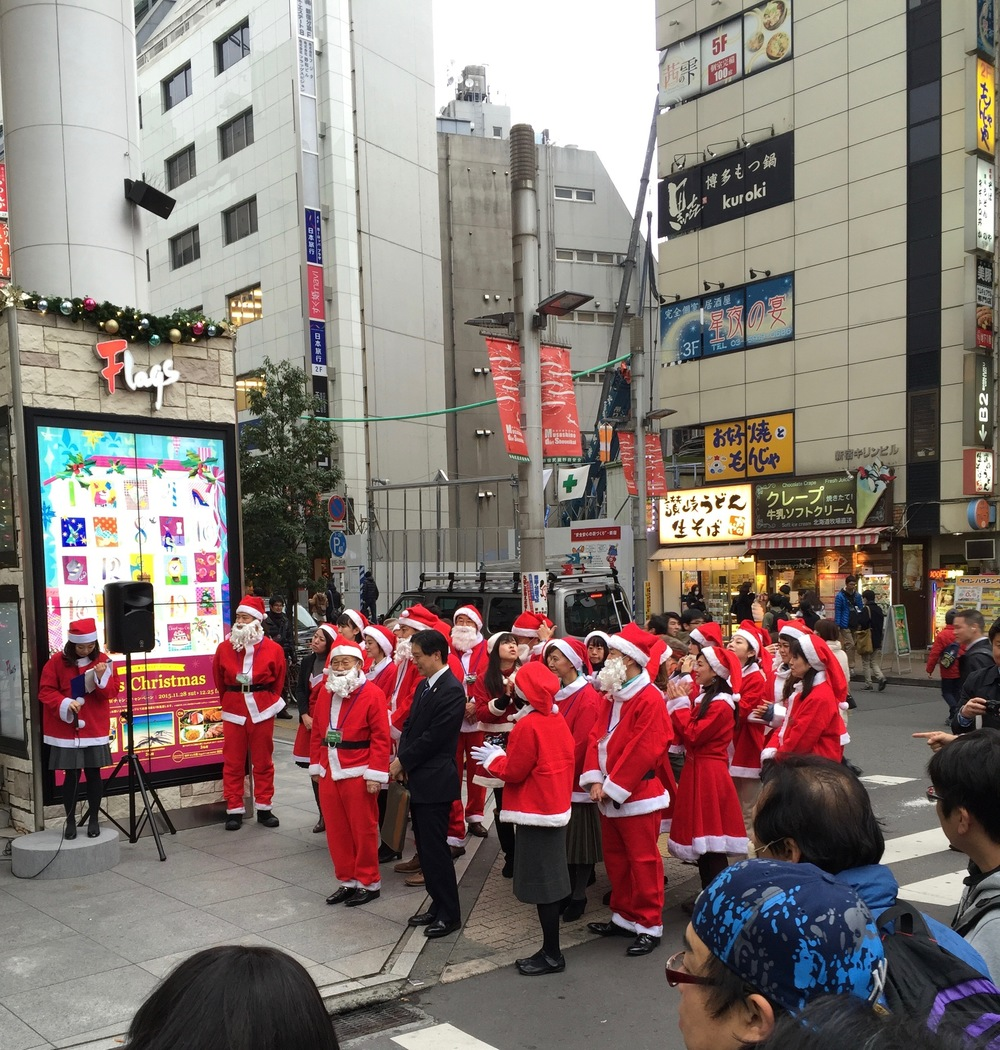 A bunch of Santas singing Christmas carols in Japanese