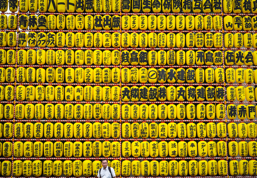 a gentleman stands in front of the giant wall of lanterns