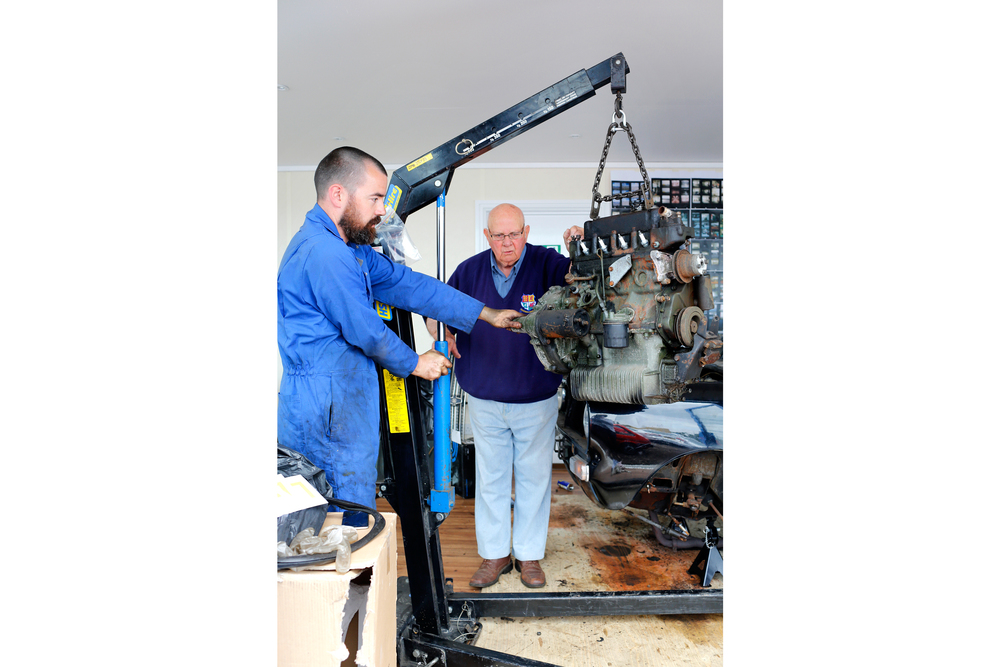 Artist Stuart Whipps working with former Longbridge car factory worker Keith Woodfield as they remove the engine from the car.