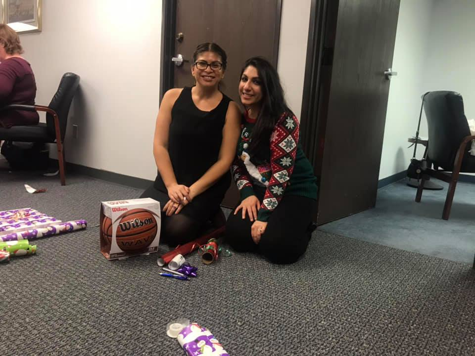 Inn member Rabia Chaudhry (right) takes a break from wrapping gifts to pose for a picture.