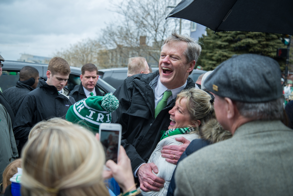 Massachusetts Gov. Charlie Baker laughs with a parade-goer on St. Patrick's Day in 2015 in Boston.