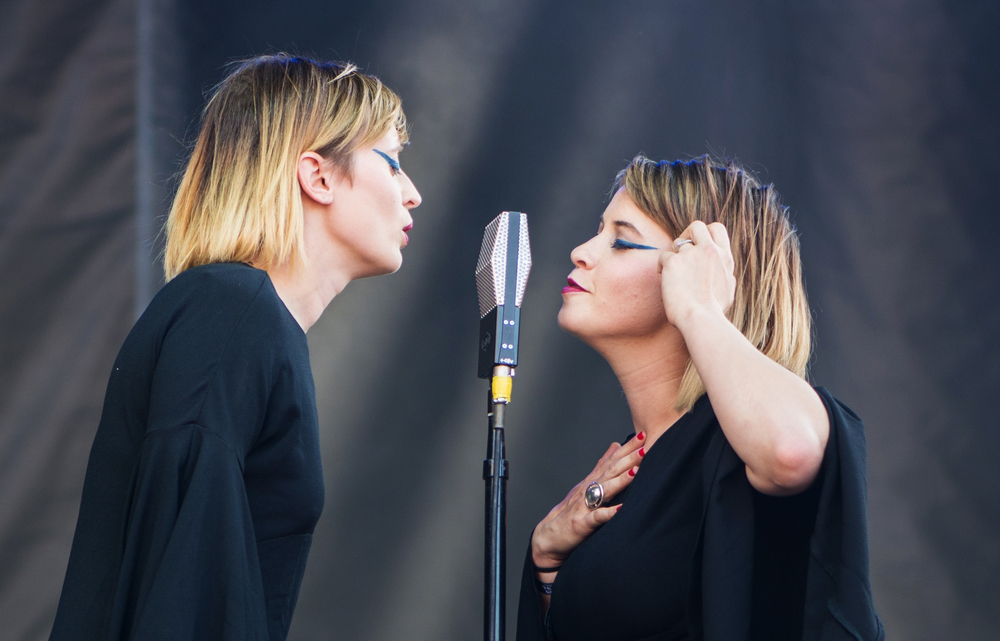 Lucius members Jess Wolfe, left, and Holly Laessig, right, sing into a ribbon microphone on stage at Boston Calling music festival on Sunday, May 23, 2015.
