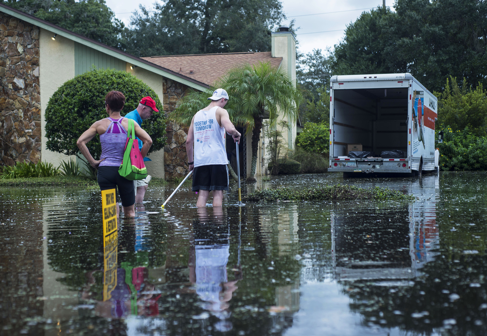 "Jim Slagle and his son, Zach Slagle, sift through their flooded yard in preparation to leave their house in Lutz, Fla. on Friday, Aug. 7. They rented a U-Haul truck to pack up their belongings. ""I don't know how to describe it other than beyond stressful,"" Jim Slagle said."