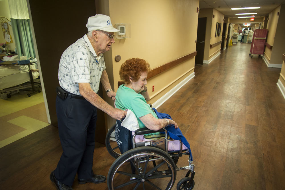 John Breslin wheels Rita Breslin, 87 and right, to the activities room at Palm Garden Nursing Home in Sun City Center on Thursday, Aug. 27.