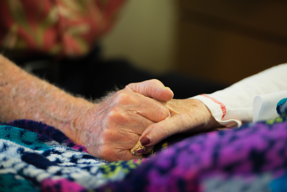 John Breslin, 90, holds hands with his wife, Rita Breslin, 87, at Palm Gardens Nursing Home in Sun City Center on Tuesday, Aug. 18. Rita lost her legs to Peripheral Arterial Disease, where blood flow loses circulation in the extremities. John and Rita said they used to dance every Saturday night.