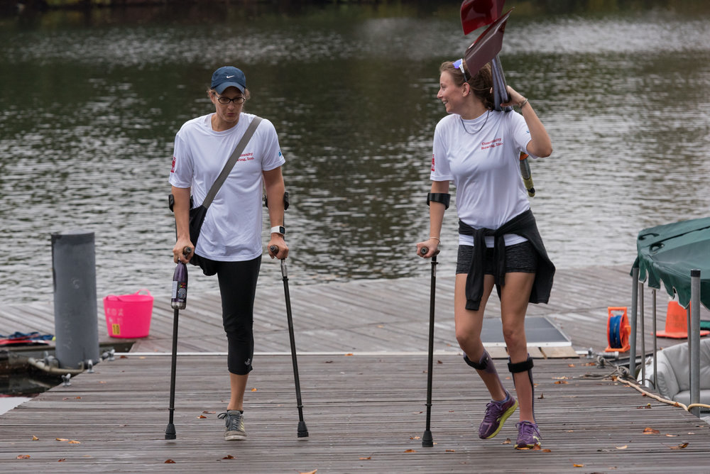 "Left to right, Johanna Beyer, 35, and Kate Barrett, 24, talk after rowing practice on Tuesday, Oct. 18 outside Community Rowing, Inc.'s boathouse. Beyer competed in inclusion doubles on the morning of Sunday, Oct. 23 and Barrett competed in inclusion fours on the evening of Saturday, Oct. 22, both in the Head of Charles Regatta.  Beyer had her leg and part of her hip amputated when she was a teenager because of bone cancer. Barrett lost most of the use of her legs after a spinal cord injury from a skiing accident when studying abroad in Spain in February, 2013. Both are members Community Rowing, Inc., which has a fairly large para-rowing membership.  ""The people here at community rowing are really supportive,"" Beyer said."