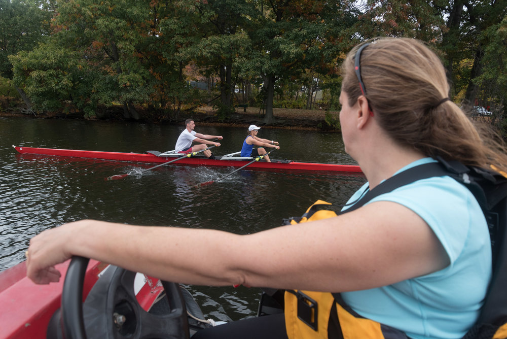"Beth Noll, right, coaches Matt Wheeler and para-rower Johanna Beyer during their practice on Friday, Oct. 21 on the Charles River. Noll said that when Beyer competed in the 2015 regatta, she was noticed by the Austrian national team, her home country.  ""Johanna saw what it meant to be an elite rower,"" Noll said.  Noll, CRI coach and coach of the para-advisory committee at the Head of the Charles, said that these events help para-rowers in multiple ways.  ""What [inclusion] does from a social standpoint, people will notice that national team members are rowing with para-rowers,"" Noll said.  In addition to the social advantages, it also is an extraordinary chance for improvement in the sport, Noll said.  ""You can hear [Wheeler] coaching her. To row with an elite member of the national team, that's an experience that most para-rowers will never get,"" Noll said. ""This is the fastest boat [Beyer] has ever been in. That, of course, is the goal of all of this."""