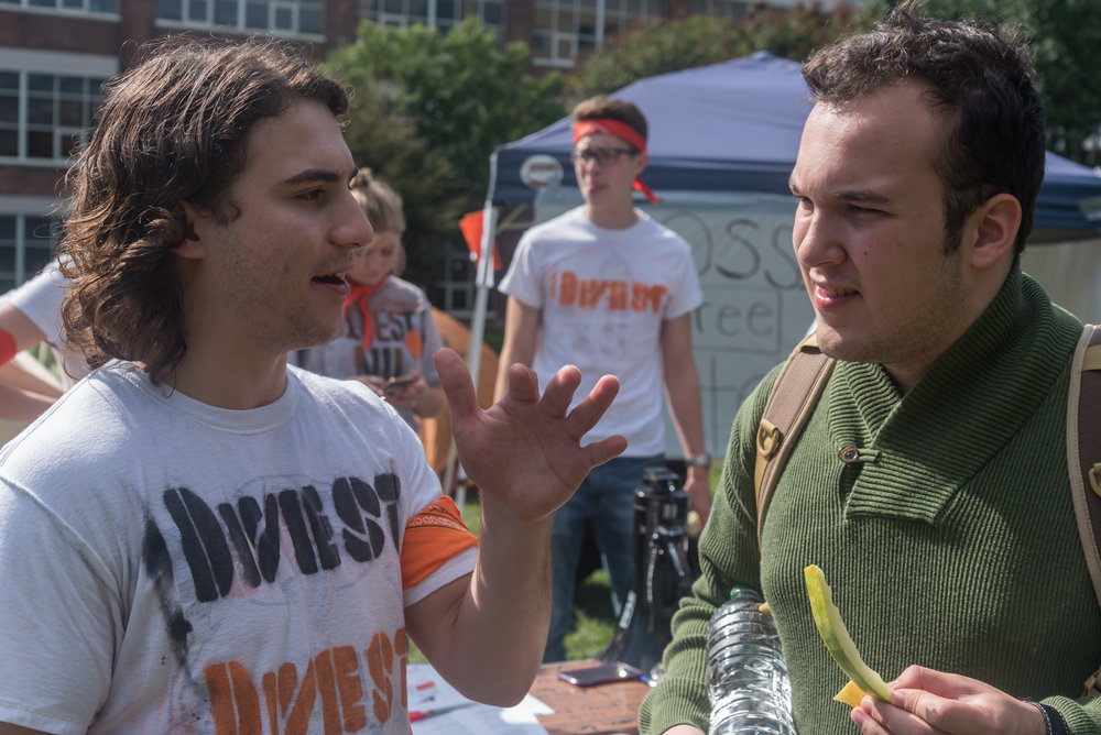 DivestNU member Charlie Cavallaro, left, talks to Northeastern sophomore Philip Wesley, right, about climate change and policy on Centennial Common on Monday, Oct. 3.