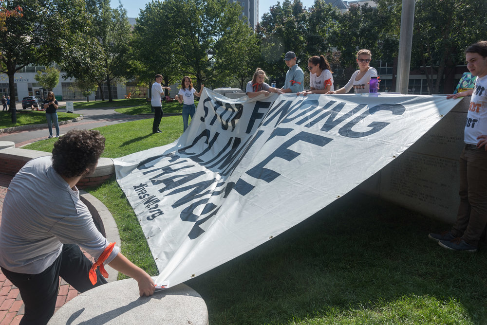 "DivestNU member and Northeastern sophomore Ben Simonds-Malamud, left, pulls a large tarp over the front of Centennial on Monday, Oct. 3. The sign reads ""Stop Funding Climate Change.""  ""[Northeastern] basically said as long as we're peaceful and nonviolent ... they're not going to evict us,"" Simonds-Malamud said."