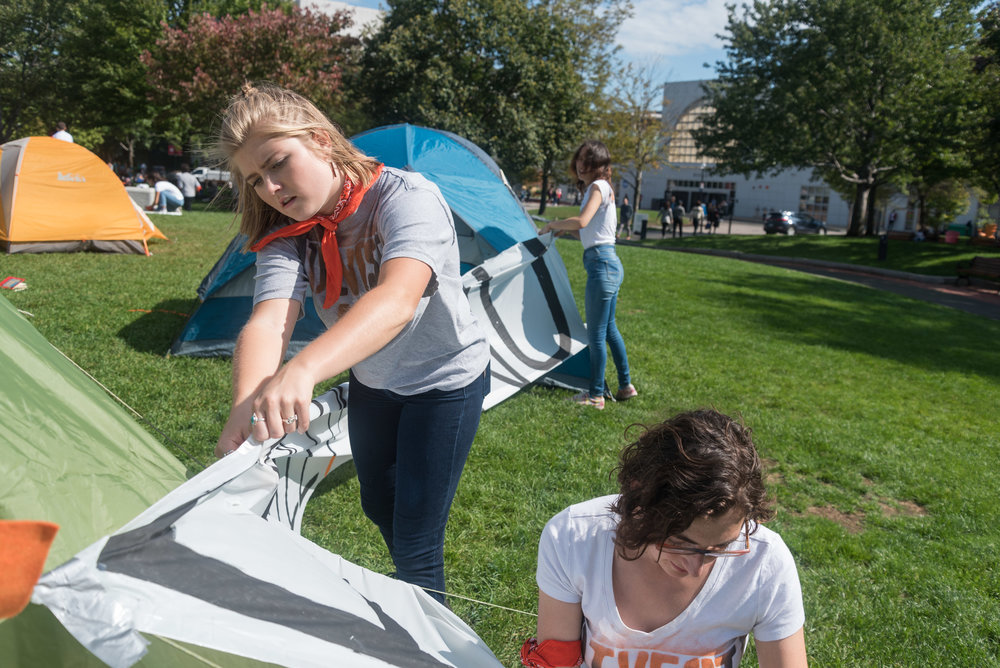 "DivestNU members Savannah Kinzer, left, and Alissa Zimmer, right, tape a sign to tents during a protest on Centennial Common on Monday, Oct. 3.   ""I've been part of [DivestNu] since my freshman year. I think over the years seeing how this issue has brought together this community has inspired me to keep on going through the years and sleep out here,"" environmental studies and political science junior Zimmer said."