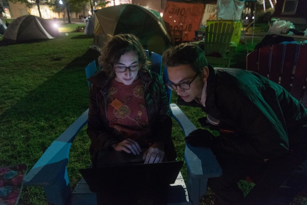 "Left to right, DivestNU members Alissa Zimmer and Nick Boyd talk on the night of Thursday, Oct. 13, 2016. As part of the group's protest, dozens of students slept on Centennial Common in tents for almost two weeks.  ""I have always been an environmentalist. I also heard ... about the divest campaign, the importance of divestment in the fight for climate justice and the administrations's refusal to work with students,"" Boyd said. ""I knew it was something that I had to get involved in."""