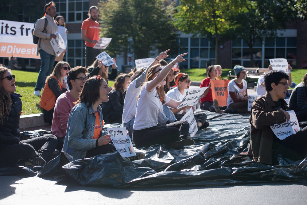"DivestNU members chant at passing prospective student groups on Saturday, Oct. 15, 2016.  ""Climate change is violent, so is Northeastern's refusal to divest,"" the students said."