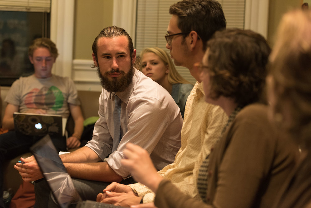 "DivestNU co-founder Austin Williams, left, listens to member Alissa Zimmer as they discuss their plans to protest the 2016 State of the University event on the night of Tuesday, Oct. 18, 2016. The meeting served as both planning and debriefing for the end of their encampment in Centennial.  ""We wanted to take some time to reflect on [the occupation,]"" Williams said during the meeting."