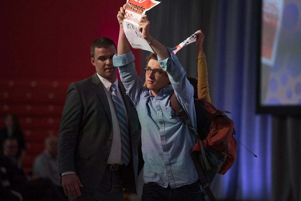 "DIvestNU members James DeCunzo, in view, and Nebai Hernandez are escorted by security back to the audience after attempting to obscure camera views of the 2016 State of the University stage in Cabot Center on Thursday, Oct. 20.  ""I knew security would be on me in a matter of seconds, but I also knew the importance of our action,"" DeCunzo said. ""I remember how much my hands were shaking after security had pulled me to the side -- not from fear, but from excitement."""