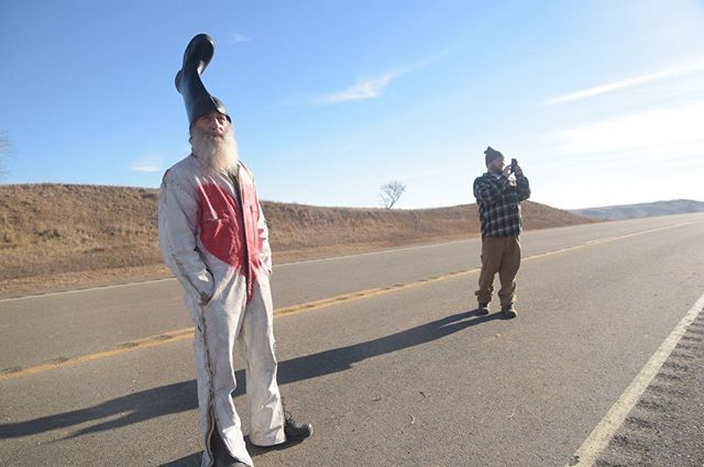"Presidential candidate Vermin Supreme, left, and his nephew Jake Taylor, right, look on a burnt car and electronic road sign near a blockade at Backwater Bridge at Cannonball, N.D. on Saturday, Nov. 26. ""I'm the people's candidate and I'm here to join the people's struggle,"" Supreme said."