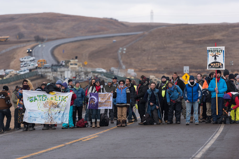 CANNON BALL, North Dakota — Protesters wait before a prayer ceremony on Thursday, Nov. 24 near Backwater Bridge in Cannon Ball, N.D. The $3.8 billion pipeline, a project by Energy Transfer Partners, threatens their water supply as well as running over sacred burial grounds on Turtle Island.