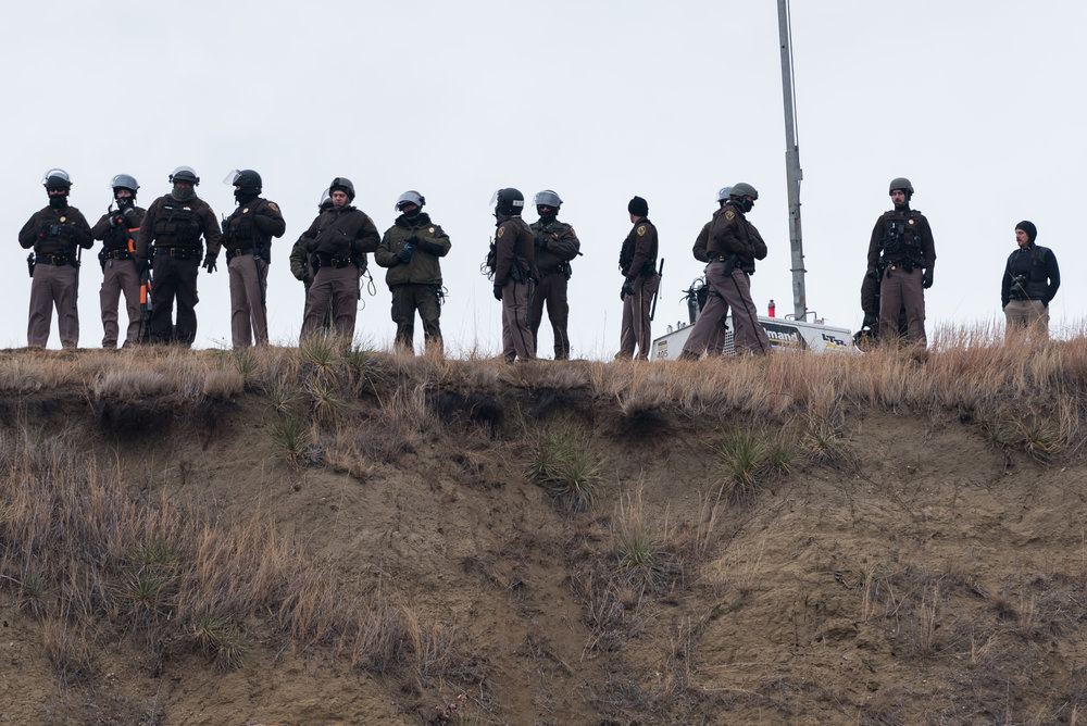 CANNON BALL, North Dakota — Morton County Sheriff's Department officers and North Dakota state troopers on Turtle Island look down at water protectors on Thursday, Nov. 24. Although interactions with police had been violent at times, the demonstration on Thanksgiving Day was peaceful, with no injuries.