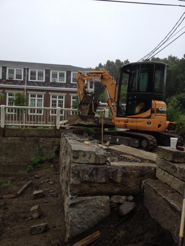 Excavator moving Granite into place