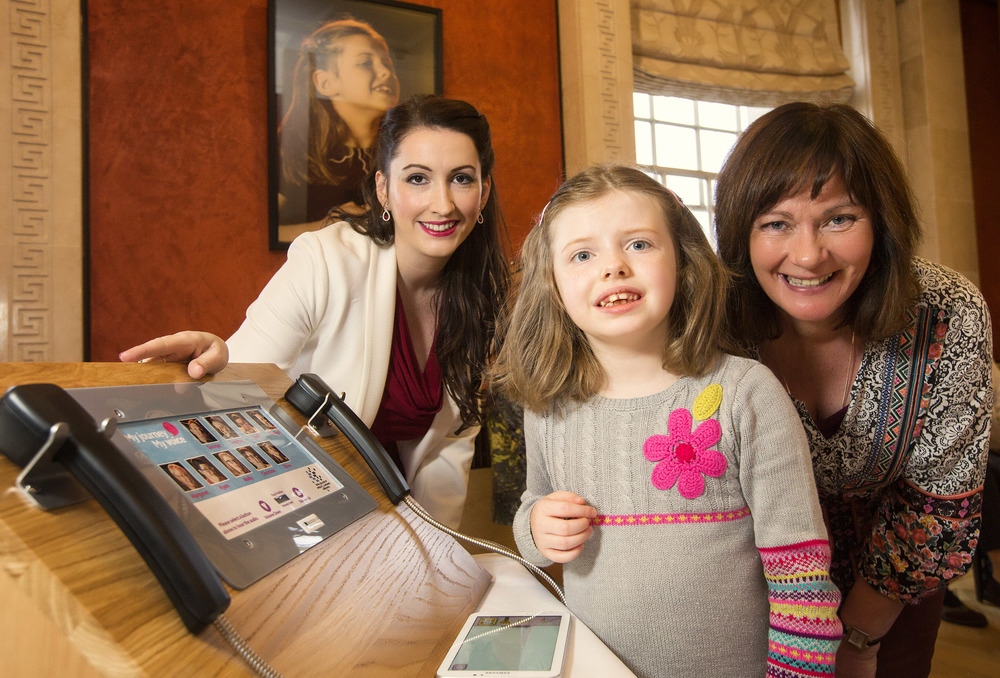 Junior Ministers Emma Pengelly (left) and Jennifer McCann (right) pictured with Olivia Curran (centre) launching the Royal College of Speech and Language Therapists 'My Journey, My Voice' multimedia portraits and stories exhibition to raise awareness of communication disability at Parliament Buildings, Stormont.