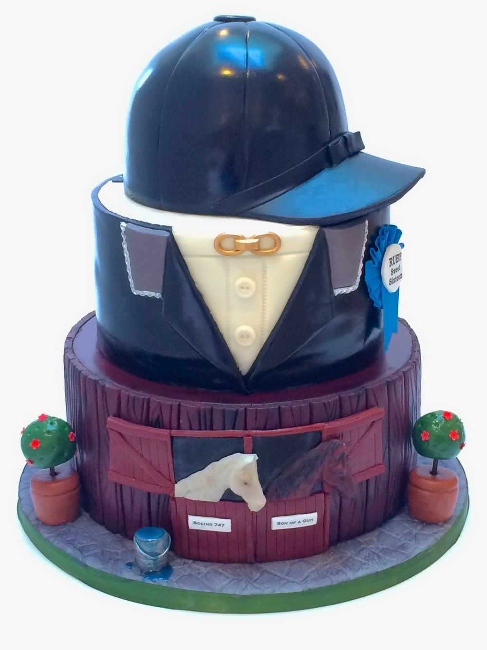 Equestrian Riding Cake, depicting a riding hat, on top of a riding jacket, on top of a barn with horses