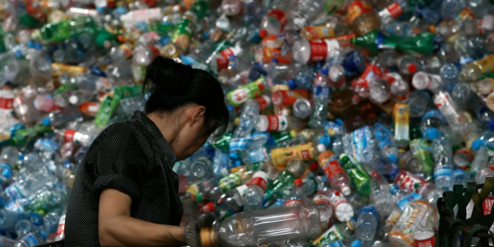 A sorter in China makes her way through a wall of imported plastic trash.