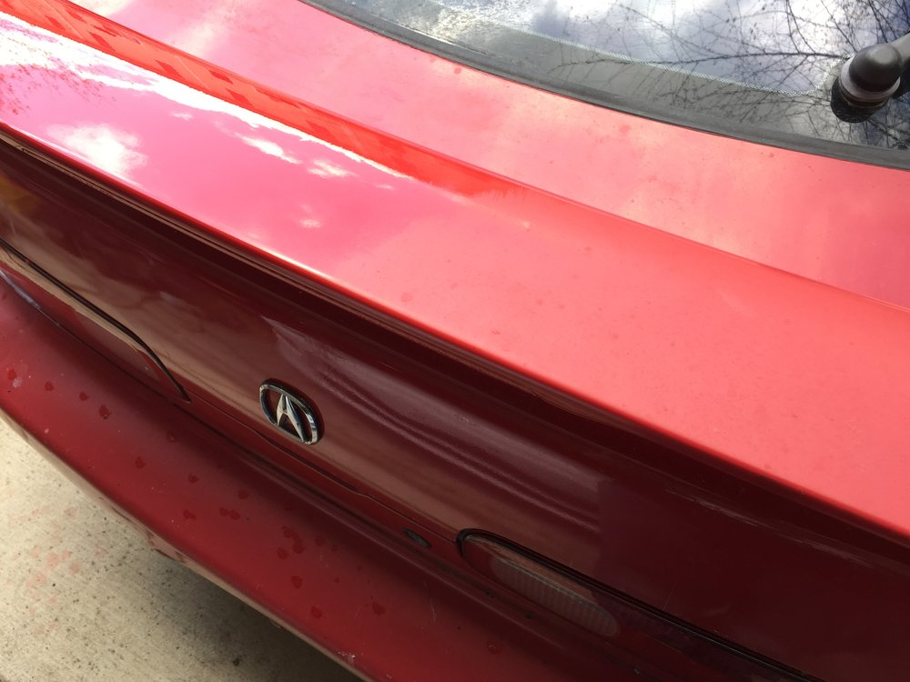 The heavily oxidized, dull single stage paint on this red Acura was wet-sanded, treated with a pure moisturizing polish, and then machine polished to a vibrant shine.