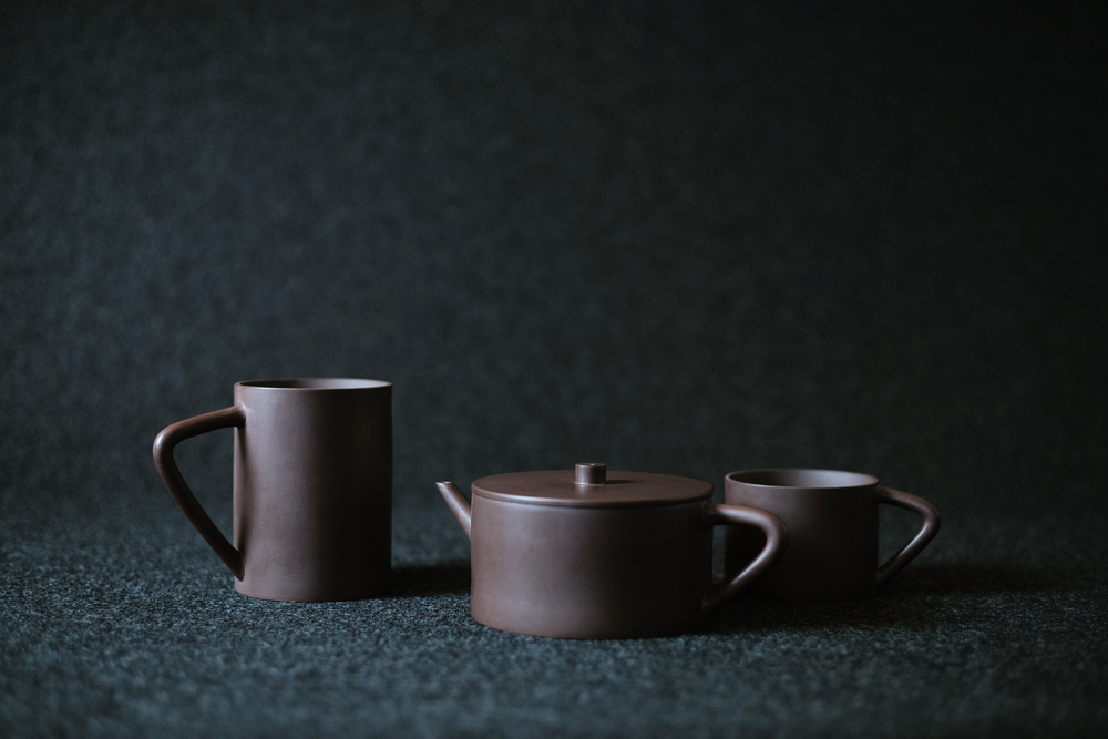 THE BAMBOO SERIES     Yixing is famous for its beautiful natural landscapes. This series is inspired by The Sea of Bamboo, one of the most attractive sceneries in the area. Modernizing the traditional purple clay teapot, the spout, handle, and strong vertical axis borrows from the structure of bamboo branches. These cups stack into one another, which not only creates space saving during storage, but references ancient water drinking practices of cutting a piece of bamboo stalk for daily use.