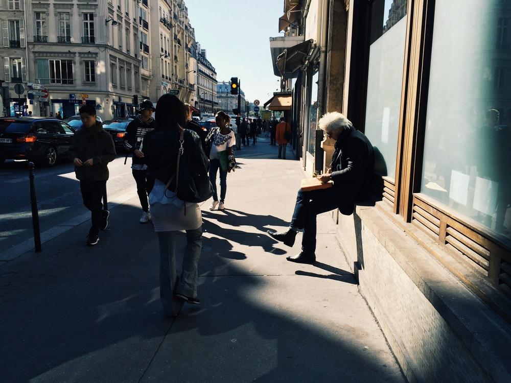Статный парижанин в летах за прочтением утренней газеты и поеданием пиццы прямо из коробки на улице.