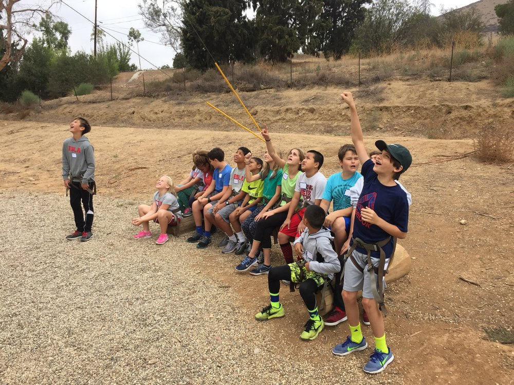 ESLA's Sixth Grade students watching a classmate on the climbing wall during their class retreat.