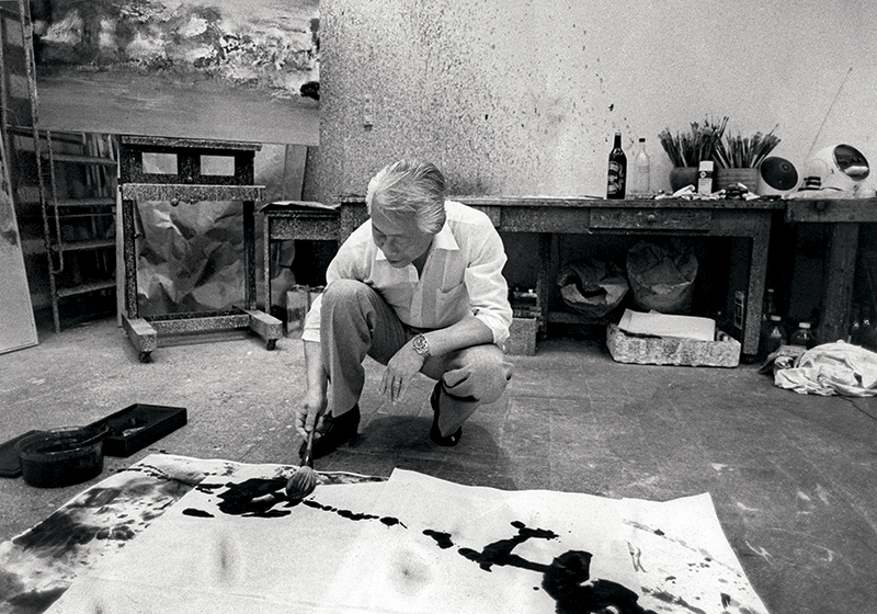 Peignant une encre de Chine dans son atelier de Paris, 1981. Photo Serge Lansac