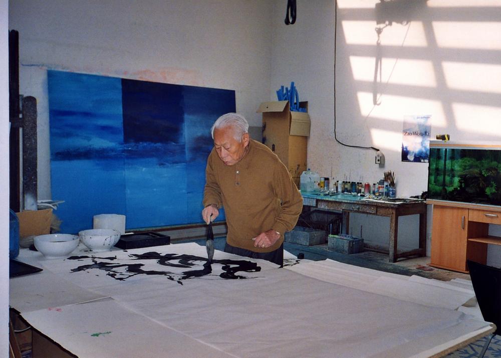 Dans l'atelier de Paris en 2006, peignant une grande encre de Chine. Au mur, son dernier triptyque 19.03.2006 – Triptyque. Photo Françoise Marquet