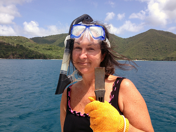 Handy Deb dives on the boat to clean growth out of the raw water intake.