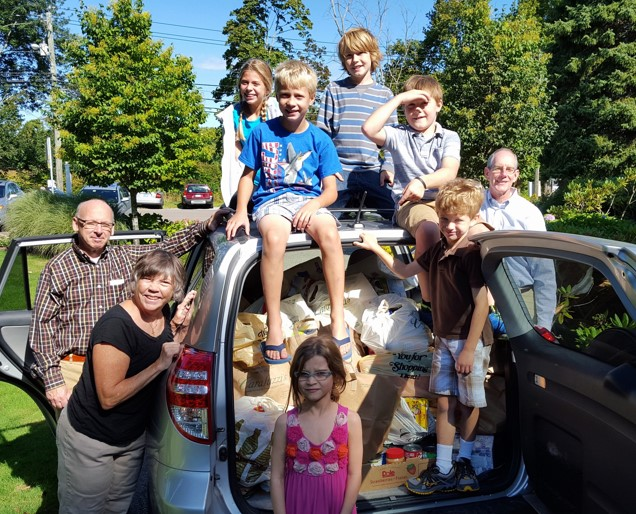 Kids and adults pose after helping load bags and bags of groceries destined for the Redding food pantry.