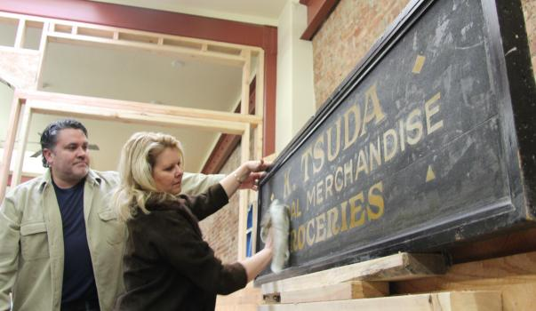 Owners Patty and John Dooley clean and restore the original Tsuda store signage in preparation for installation inside the restaurant. Photo courtesy of the Auburn Journal