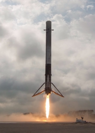 SpaceX booster lands for re-use after launching a Falcon 9 rocket.