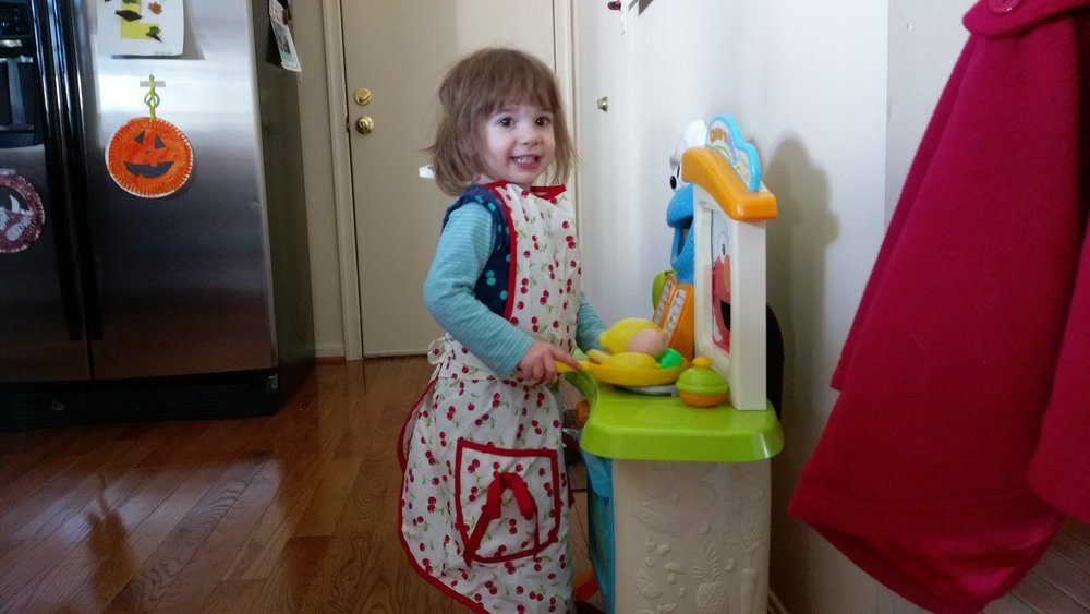 Cece just doing some cooking wearing her Mommy's apron