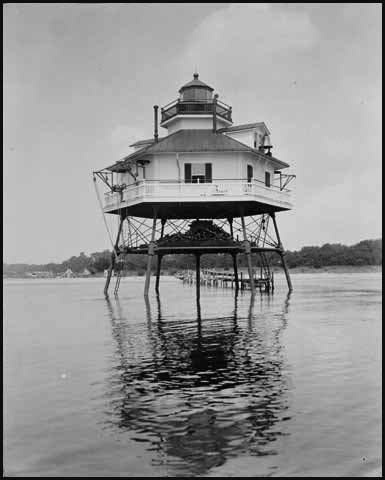 This early photo of the lighthouse shows a long pier stretching from the beach (photo from the Mariners Museum)