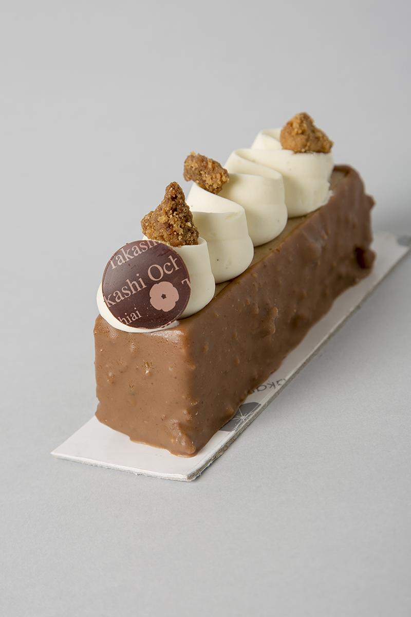 Toke.Dacquoise d'avellana, cruixent de gianduja i neula, cremós de xocolata i cafè, mousse de gianduja, bany de xocolata amb llet i neula i ganache de vainilla amb espècies de fava tonca.