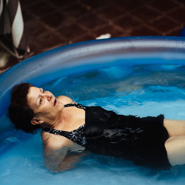 One of Parkinson's lesser-known symptoms is thermoregulatory dysfunction. This image, which is part of my project 'Oltremare', depicts my mother bathing in a pool of hot water, which feels yet too cold to her. Her elbows are locked behind her back to find balance and her body is rigid due to muscular spasms. Her face, with her mouth half open and her eyes looking up at the sky, shows an expression of suffering and joy coming together and coexisting.