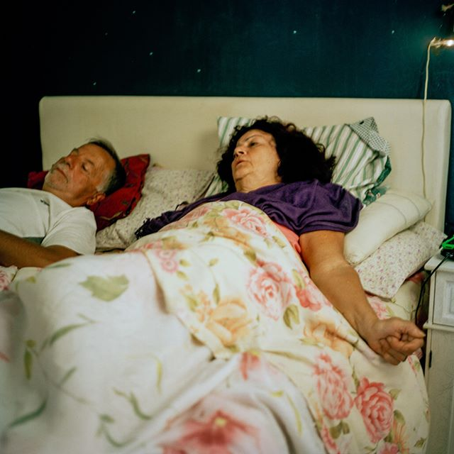 A small but relevant detail in this photo is my mother's arm, extended out of the bed, with her hand clenched in a fist. Muscle cramps in Parkinson's are generally caused by muscular rigidity and reduced movement (bradykinesia) rather than by muscles contracting. In this photo, my father is keeping my mother company, watching TV with her while she tries to get distracted from the cramps. • • • • •