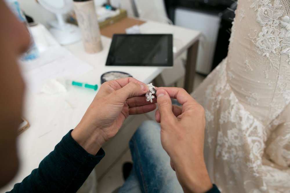 A world class seamstress adding an embellishment to a bridal gown.   Photography by David Bachar.