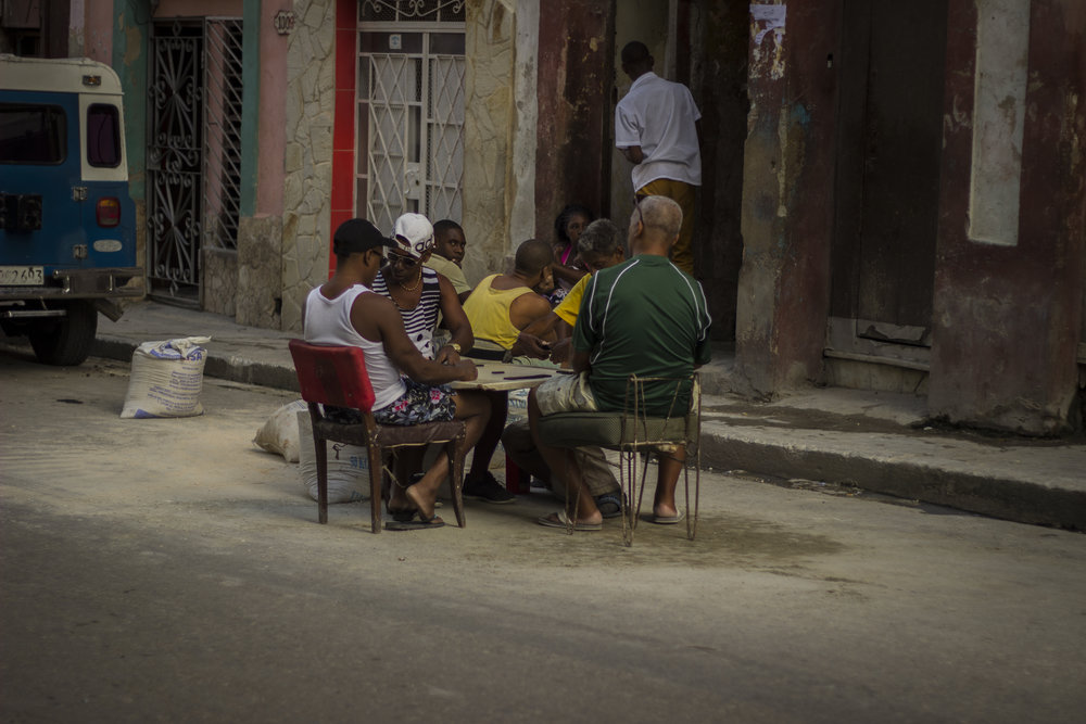 The streets are bustling with characters: people playing dominoes wherever a table and chairs can fit
