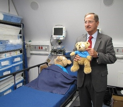 Bob Ranck, President and CEO of ORBIS International, demonstrates the usefulness of the Omega teddy bears in the recovery room of the MD-10 aircraft. ORBIS carries 700-pounds of teddy bears during a typical mission.