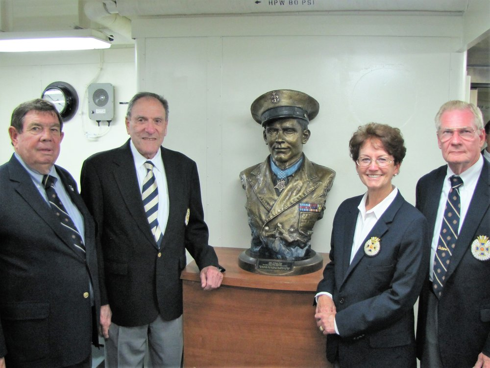 NOUS Representatives with bust of Chief John W. Finn, from left to right: RADM Doug Moore; CAPT Al Serafini; Commander General CAPT Michele Lockwood; CAPT Sandy Lockwood