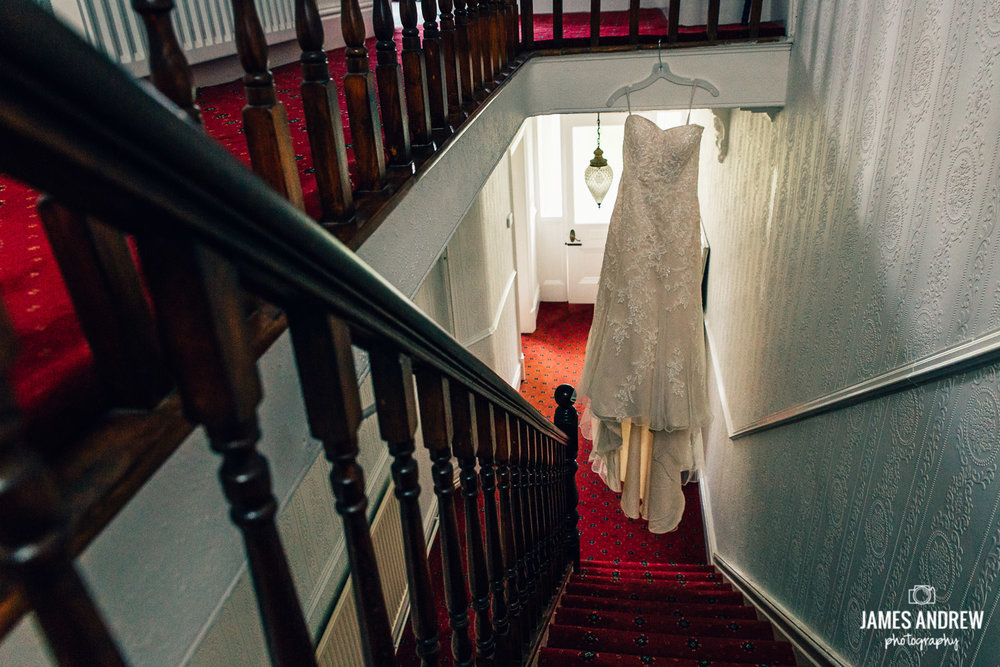 white Wedding dress hanging on stairs