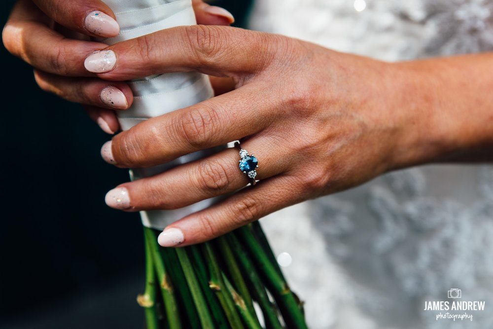 close up of brides hand holding flowers blue engagement ring stone