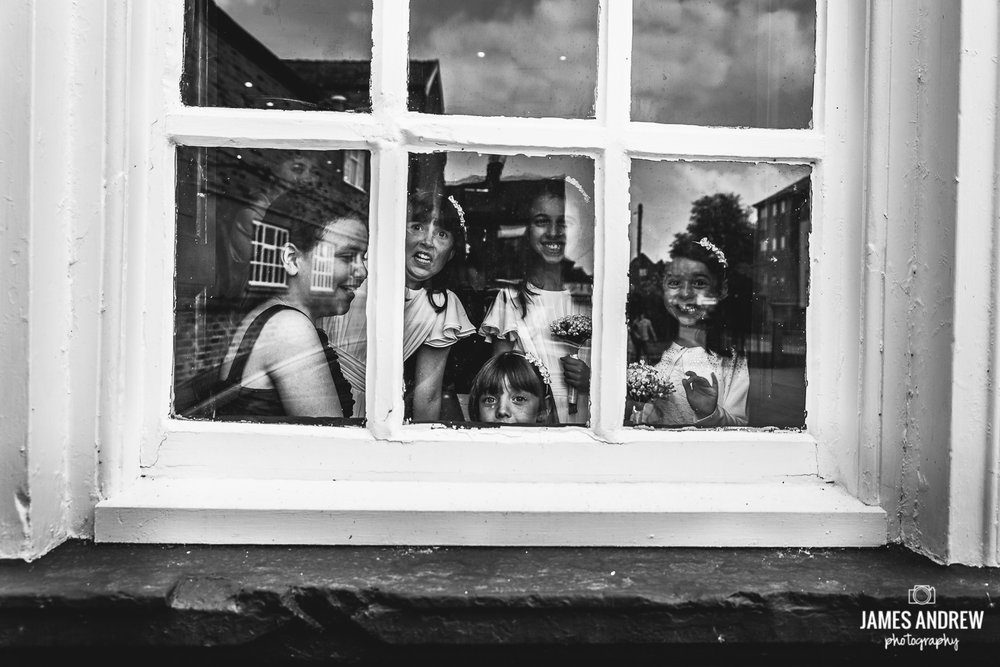 bridesmaids looking through window at camera