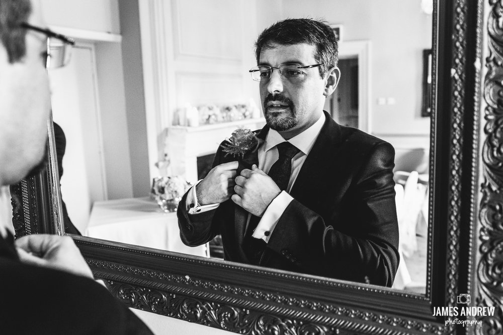 Groom looking in mirror before getting married
